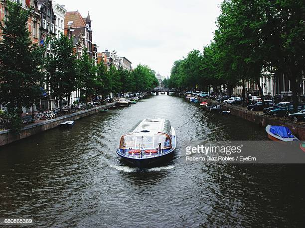 Boat On Canal Amidst Trees In City