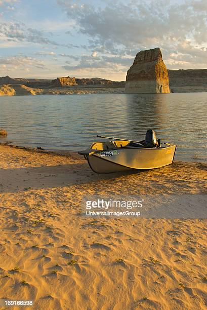 A boat on the beach at sunrise on Lake Powell with LOne Rock in the background Part of the Glen Canyon National Recreation Area that is spread across...