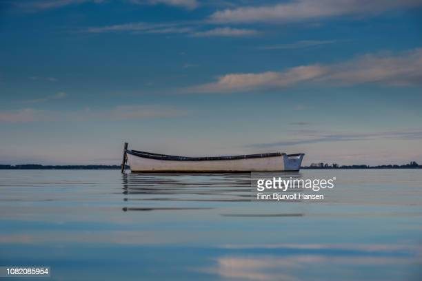 boat on the lake lesina in italy photographed in a low angle - finn bjurvoll stock photos and pictures