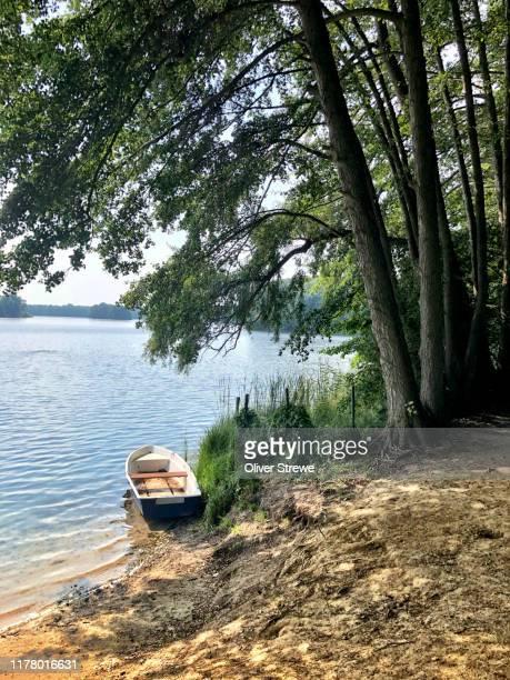 boat on the shore at a berlin lake - seeufer stock-fotos und bilder