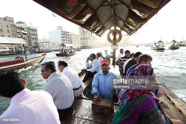 A boat operator ferries tourists on his water taxi also known as an Abra along a waterway in Al Ghubaiba's creek district of Dubai United Arab...