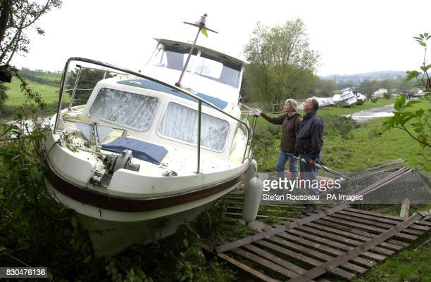 Boat owners in Wateringbury Kent survey the damage to their boat after the River Medway burst its banks Five rivers in Kent were being kept on Severe...