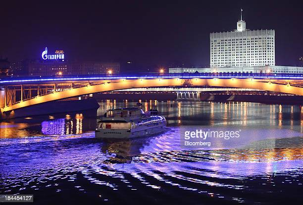 A boat pass beneath a bridge on the River Moskva beyond the Russian White House right and an illuminated OAO Gazprom advertisement in Moscow Russia...