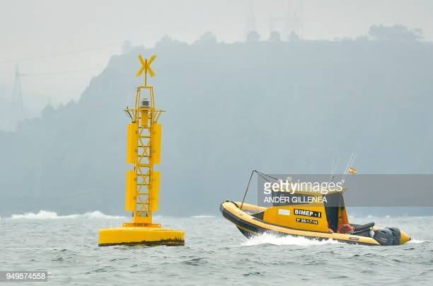 boat passes by a buoy near the Spanish Basque city of Lemoiz on April 20 2018 The floating device creates energy from the waves