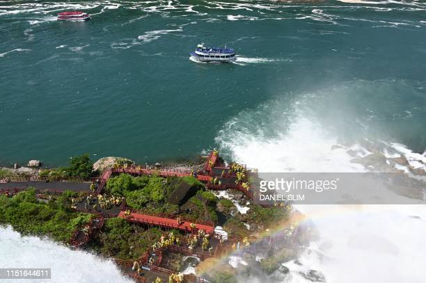 A US boat passes by a Canadian boat as the American Falls are seen from the US side at Niagara Falls State Park in Niagara Falls New York on June 22...