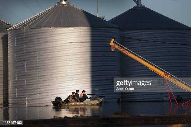 A boat passes by grain bins which are surrounded by floodwater on March 21 2019 in Craig Missouri The town of Craig is completely surrounded by...