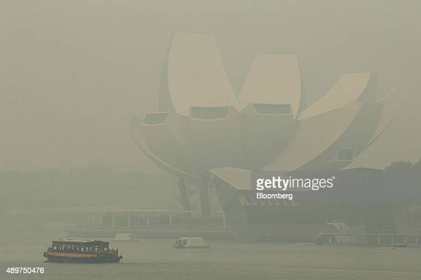 Boat passes by the Art Science Museum, which stands shrouded in smog, in the Marina Bay district in Singapore, on Thursday, Sept. 24, 2015. The haze...