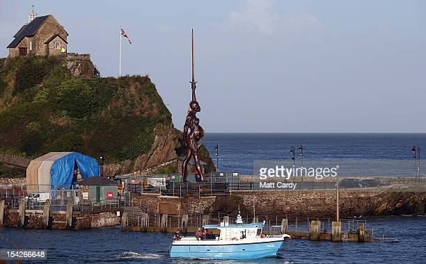 A boat passes in front of Damien Hirst's bronze sculpture of a pregnant woman on October 17 2012 in Ilfracombe England The bronzeclad swordwielding...