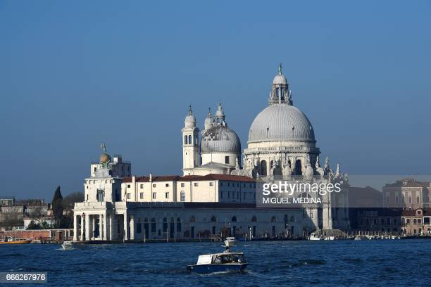 A boat passes in front of Punta della Dogana' in Venice on April 8 2017 / AFP PHOTO / MIGUEL MEDINA
