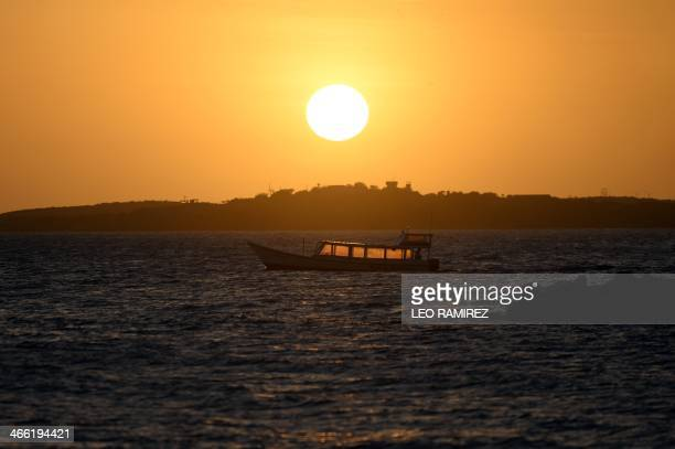 A boat passes in front of the sunset from El Yaque Beach Nueva Esparta state Margarita Island Venezuela where the 2014 Caribbean Baseball Series will...