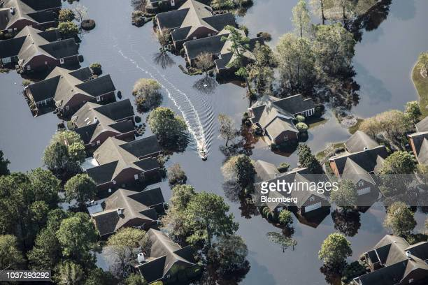 Boat passes through a flooded neighborhood in this aerial photograph taken above Wallace, North Carolina, U.S., on Friday, Sept. 21, 2018. Record...