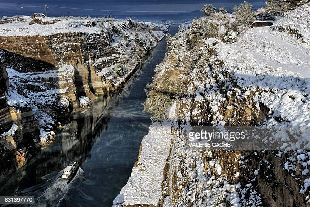 A boat passes through the snowcovered Corinth Canal near the city of Corinth on January 10 2017 A cold snap gripping Europe has killed more than 30...