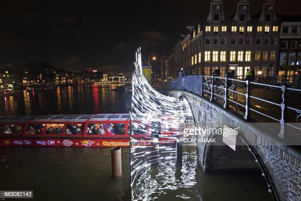 A boat passes under a light sculpture at the Herengracht in Amsterdam on November 30 2017 During the Amsterdam Light Festival there is a route of...