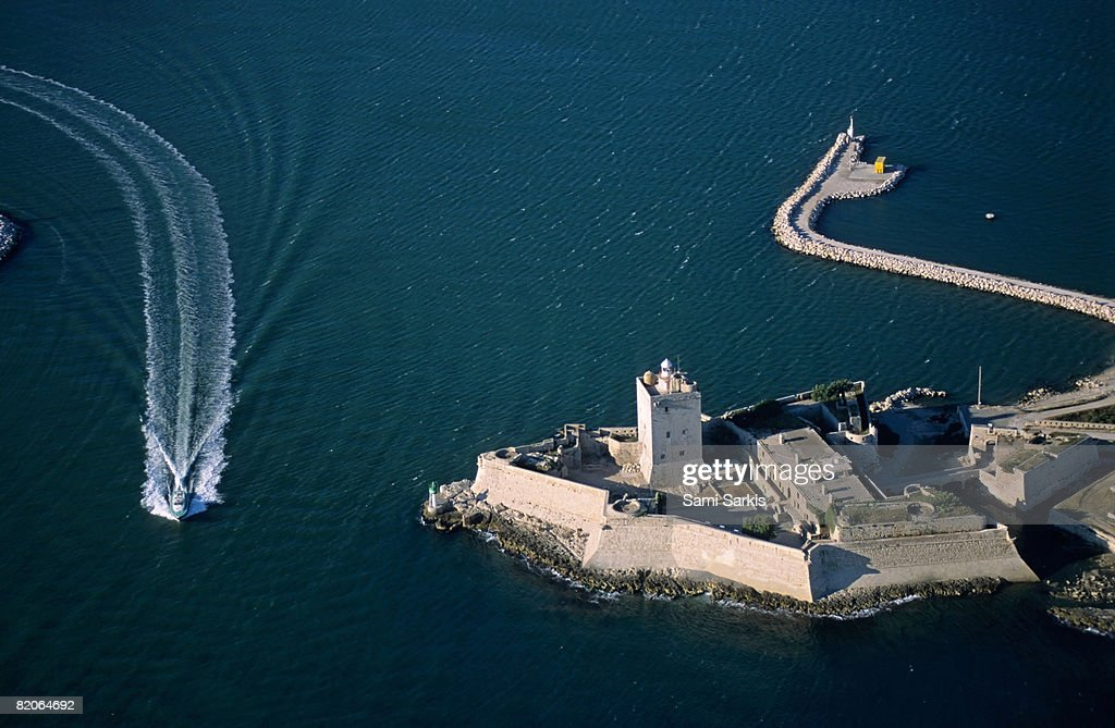 Boat passing along the fort of Fos-Sur-Mer, France (aerial view) : Stock Photo