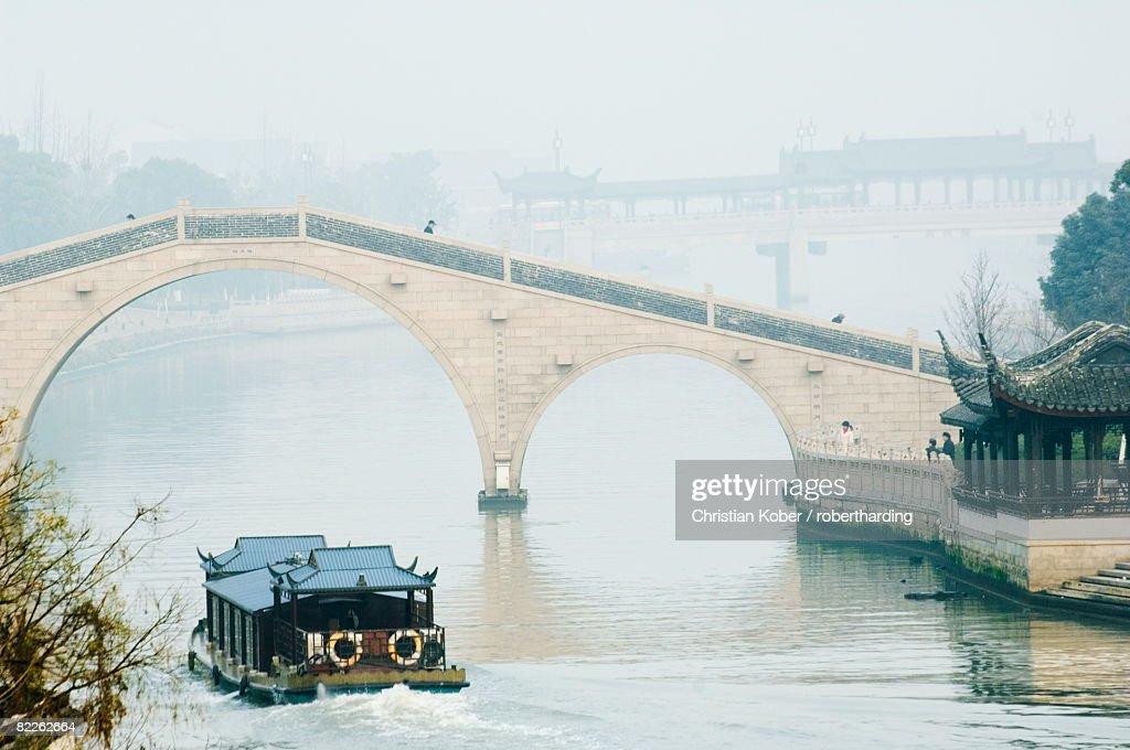 A boat passing through a stone arched bridge on Waicheng River with Wumen bridge behind, Suzhou, Jiangsu Province, China, Asia : Stock Photo