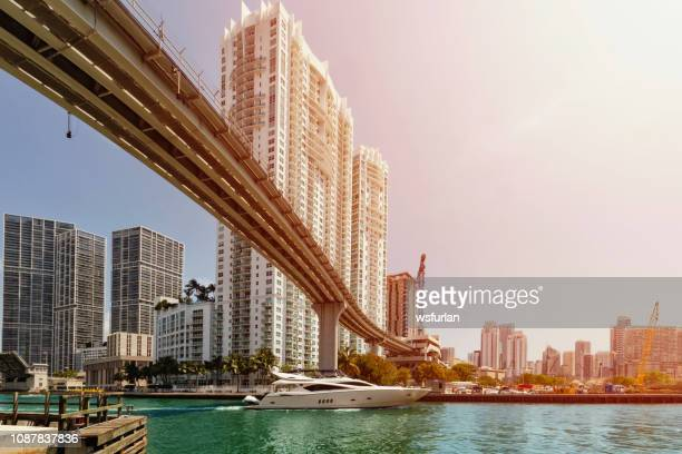 boat passing under a bridge on miami river. - downtown miami stock pictures, royalty-free photos & images