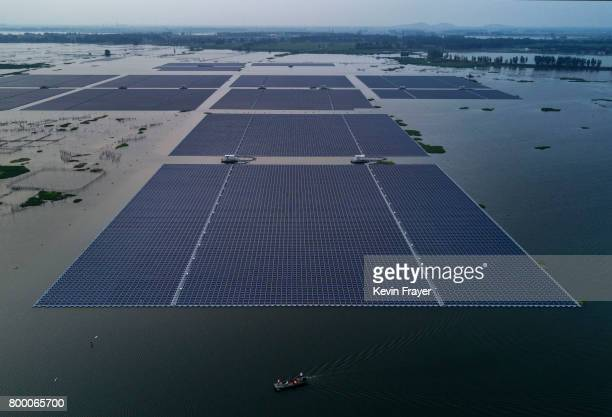 A boat pulls a group of solar panels before being connected to a large floating solar farm project under construction by the Sungrow Power Supply...