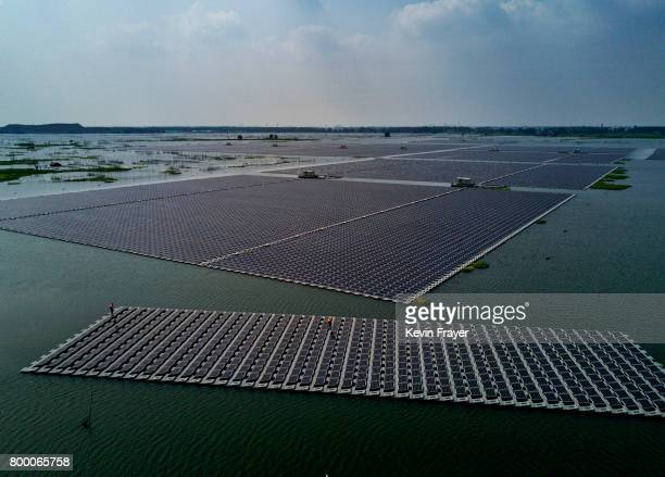 A boat pulls a group of solar panels before they are connected to a large floating solar farm project under construction by the Sungrow Power Supply...