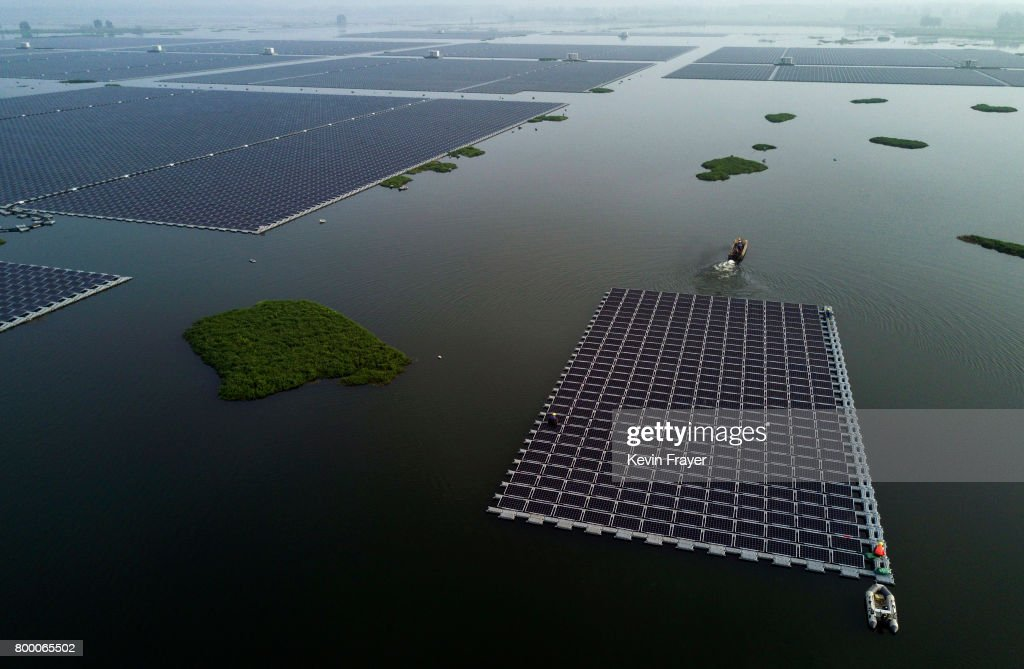 A boat pulls a group of solar panels to be connected to a large floating solar farm project under construction by the Sungrow Power Supply Company on a lake caused by a collapsed and flooded coal mine on June 14, 2017 in Huainan, Anhui province, China. The floating solar field, billed as the largest in the world, is built on a part of the collapsed Panji No.1 coal mine that flooded over a decade ago due to over-mining, a common occurence in deep-well mining in China's coal heartland. When finished, the solar farm will be made up of more than 166,000 solar panels which convert sunlight to energy, and the site could potentially produce enough energy to power a city in Anhui province, regarded as one of the country's coal centers. Local officials say they are planning more projects like it, marking a significant shift in an area where long-term intensive coal mining has led to large areas of subsidence and environmental degradation. However, the energy transition has its challenges, primarily competitive pressure from the deeply-established coal industry that has at times led to delays in connecting solar projects to the state grid. China's government says it will spend over US $360 billion on clean energy projects by 2020 to help shift the country away from a dependence on fossil fuels, and earlier this year, Beijing canceled plans to build more than 100 coal-fired plants in a bid to ease overcapacity and limit carbon emissions. Already, China is the leading producer of solar energy, but it also remains the planet's top emitter of greenhouse gases and accounts for about half of the world's total coal consumption.