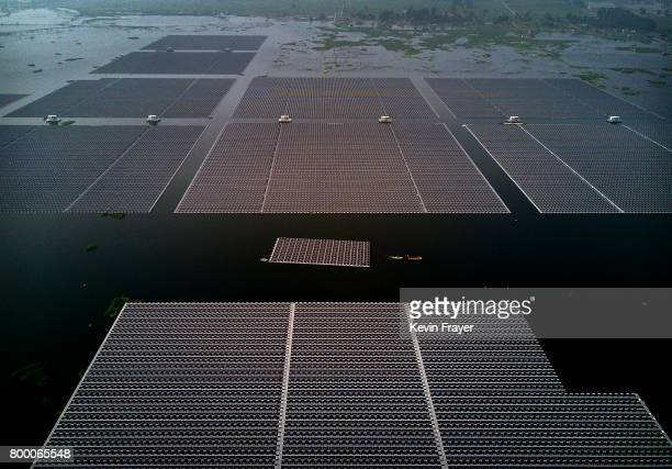 A boat pulls a group of solar panels to be connected to a large floating solar farm project under construction by the Sungrow Power Supply Company on...