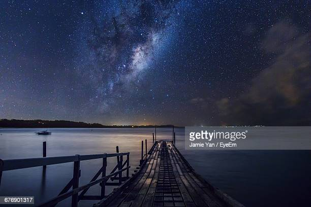 Boat Ramp Over Sea Against Star Field