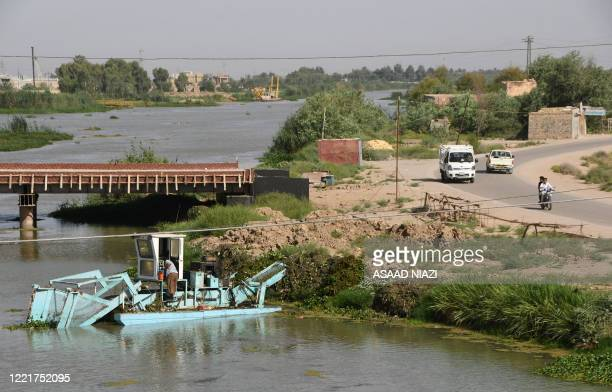 Boat removes Eichhornia crassipes, commonly known as water hyacinth, from the surface of the Euphrates river, in Iraq's Shatrah district of the...