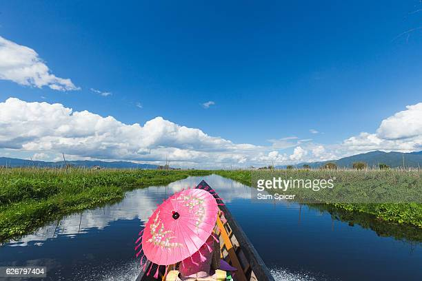 boat ride across inle lake, myanmar. lady using traditional burmese umbrella - inle lake stock pictures, royalty-free photos & images