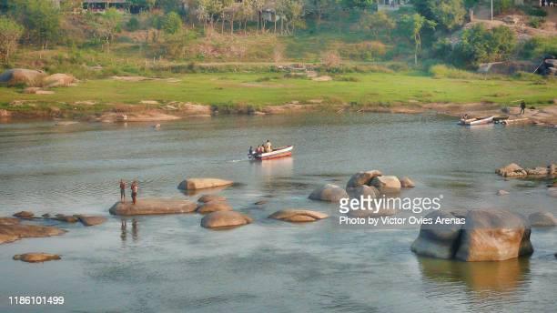 boat ride and ablutions. morning activity in the tungabhadra river in hampi, karnataka, india - victor ovies fotografías e imágenes de stock