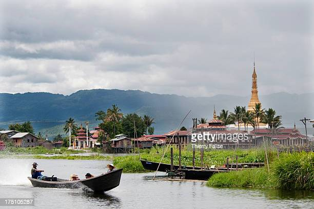 A boat rides past a Buddhist monastery on the Inle Lake