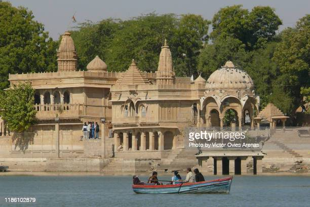 boat riding in front of the ghats and temples in gadi sagar lake in jaisalmer, rajasthan, india - victor ovies fotografías e imágenes de stock