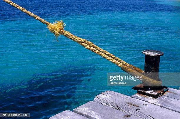 Boat rope on mooring post on pier, close up
