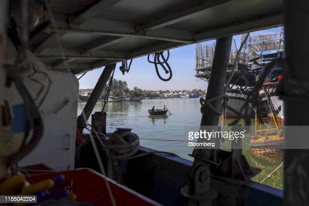 A boat rows past fishing trawlers anchored in Tan Quang harbor in Quang Nam province Vietnam on Wednesday June 26 2019 Fishermen are on the front...