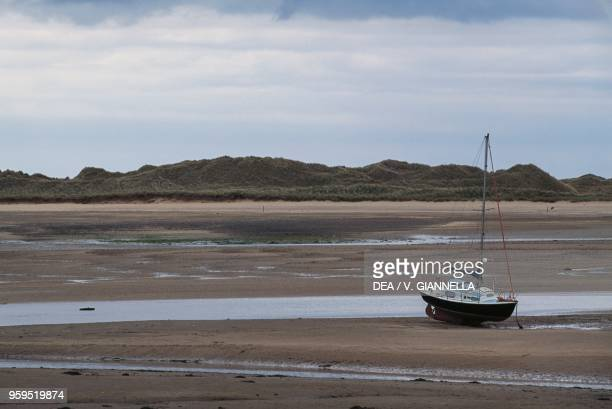 A boat run aground in Ravenglass because of the low tide Lake District United Kingdom