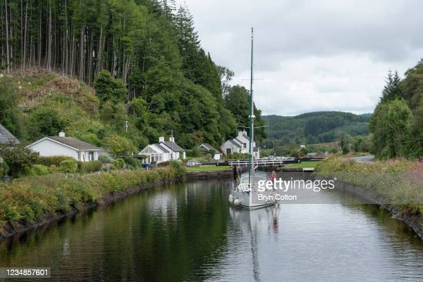 Boat sail towards the sea locks at gate eight on the Crinan Canal on August 19, 2021 in Cairnbaan, Scotland. Passage along the canal has been reduced...