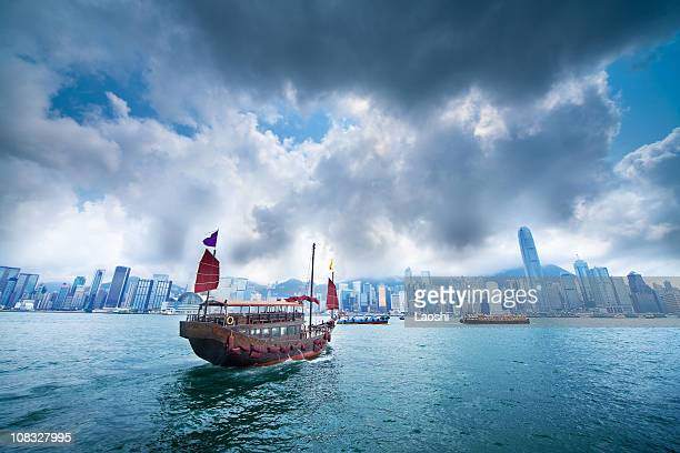 A boat sailing against a city skyline