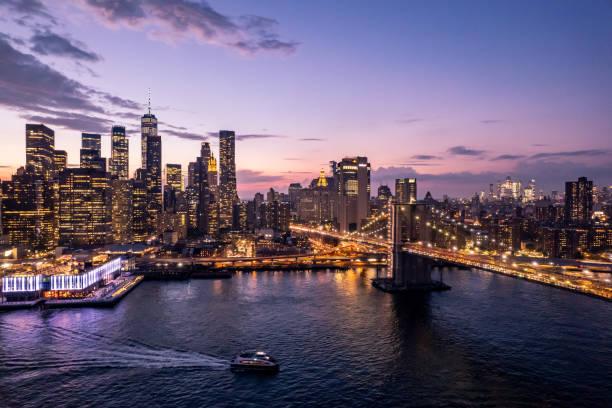Boat sailing in East River towards Brooklyn Bridge, Manhattan, New York, USA
