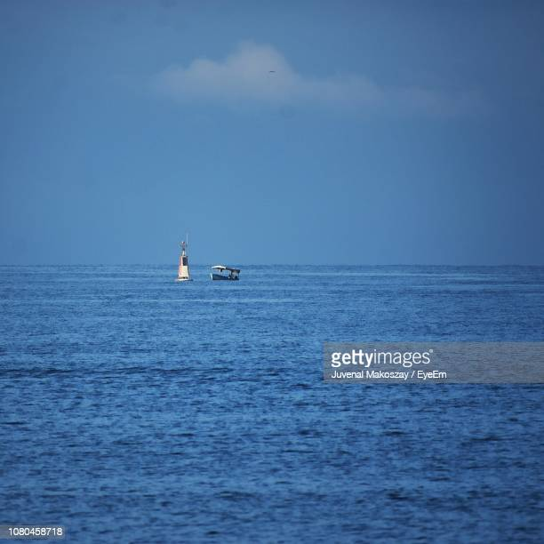 Boat Sailing In Sea Against Blue Sky