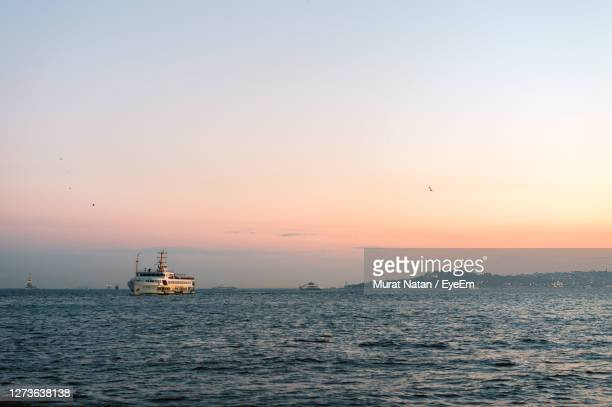 boat sailing in sea against clear sky during sunset - ferry stock pictures, royalty-free photos & images