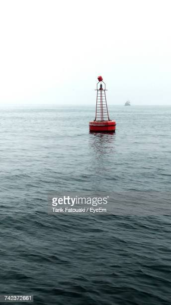 boat sailing in sea against clear sky - buoy stock photos and pictures