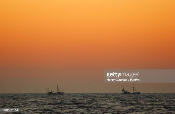Boat Sailing In Sea Against Sky During Sunset