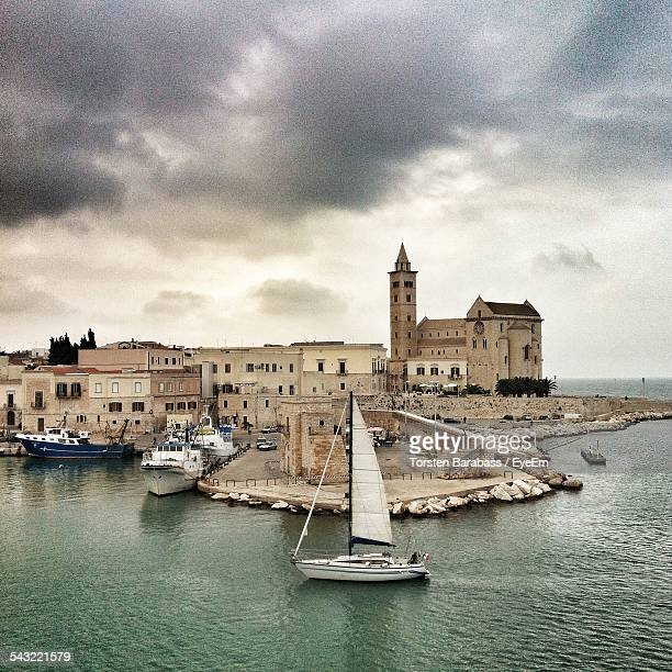 Boat Sailing In Sea In Front Of Trani Cathedral Against Cloudy Sky