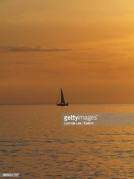 boat sailing on sea against sky during sunset - lucinda lee stock photos and pictures
