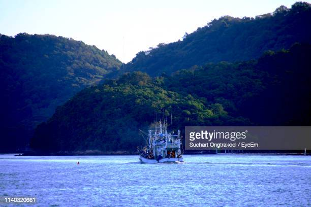 boat sailing on sea by mountain against sky - chanthaburi stock pictures, royalty-free photos & images