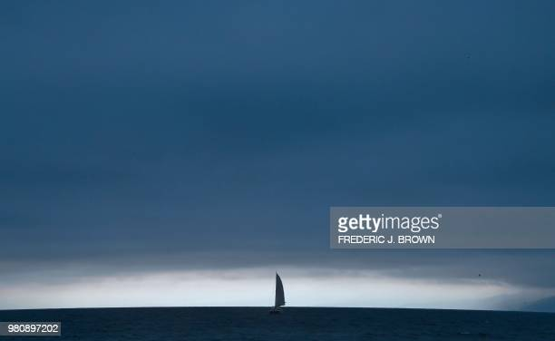 A boat sails across the horizon on an overcast evening off Santa Monica beach in Santa Monica California on June 21 on the summer solstice