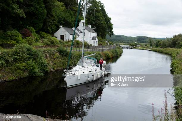 Boat sails along the Crinan Canal and past cottages on August 19, 2021 in Cairnbaan, Scotland. Passage along the canal has been reduced as water...