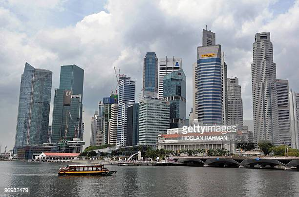 A boat sails along the Singapore river with the skyline of the financial district of Raffles Place in the background on February 19 2010 Singapore...