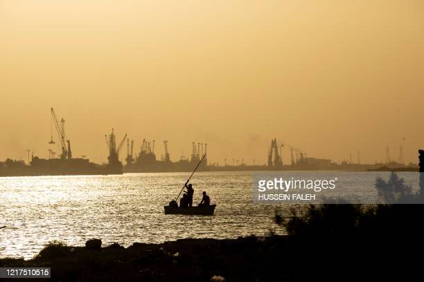 Boat sails by the Maqil port, along the Shatt Al-Arab river at sunset in the southern city of Basra, as temperatures soar in the region, on June 4,...
