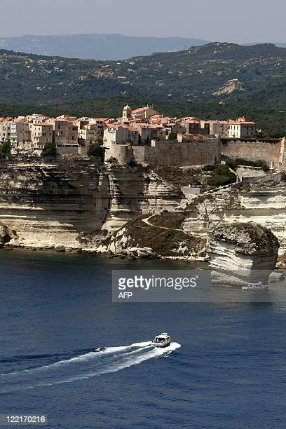 A boat sails off the cliffs of the Corsican city of Bonifacio southern France on August 25 2011 AFP PHOTO / PASCAL POCHARDCASABIANCA