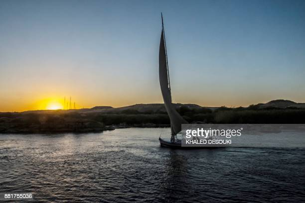 A boat sails on the Nile River as the sun sets over the Egyptian city of Aswan some 920km south of the capital Cairo on November 26 2017 / AFP PHOTO...