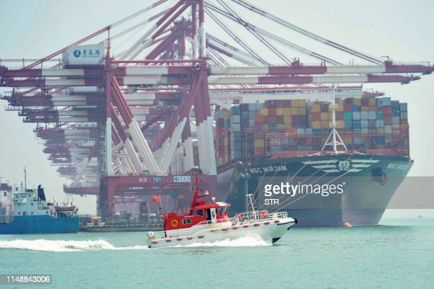 A boat sails past as a cargo ship berths at a port in Qingdao in China's eastern Shandong province on June 10 2019 China's exports beat gloomy...
